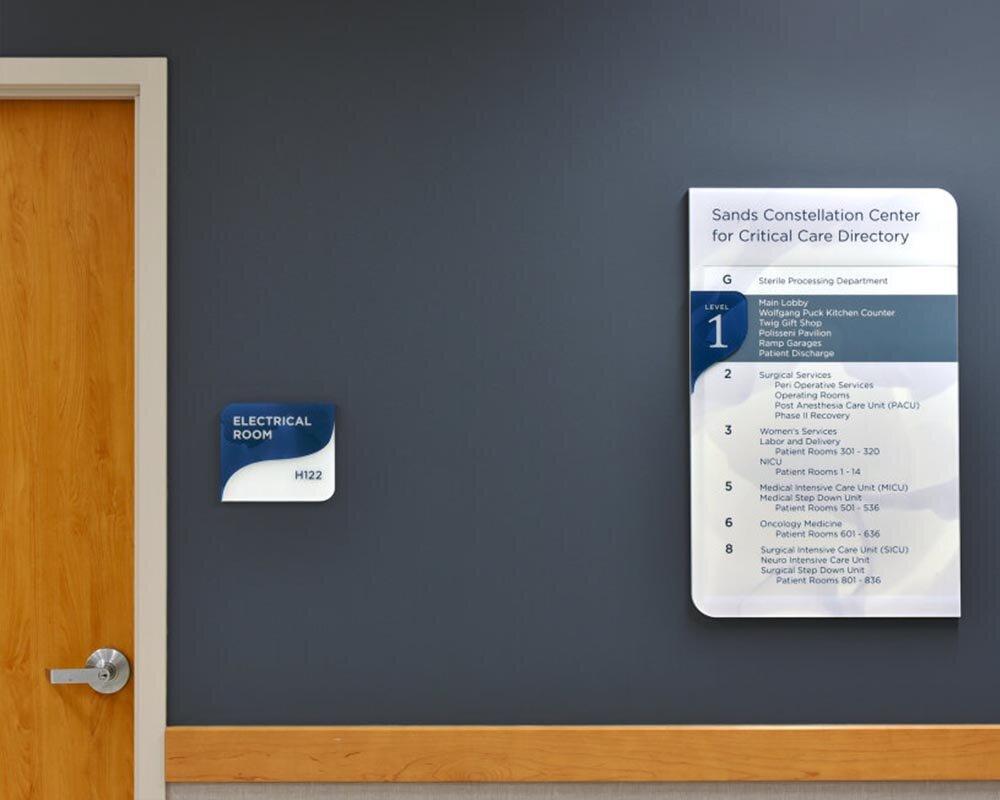 Two custom vivid signs on walls of hospital