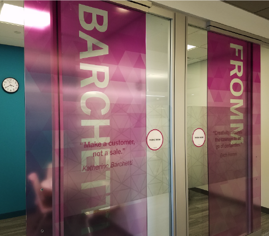 Pink and blue printed window film on sliding glass office doors in modern office