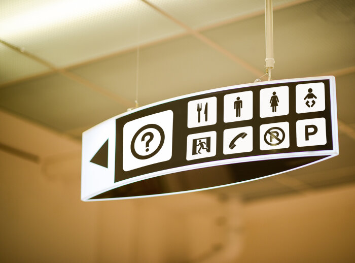 Satirical photo of overhead sign with many icons.