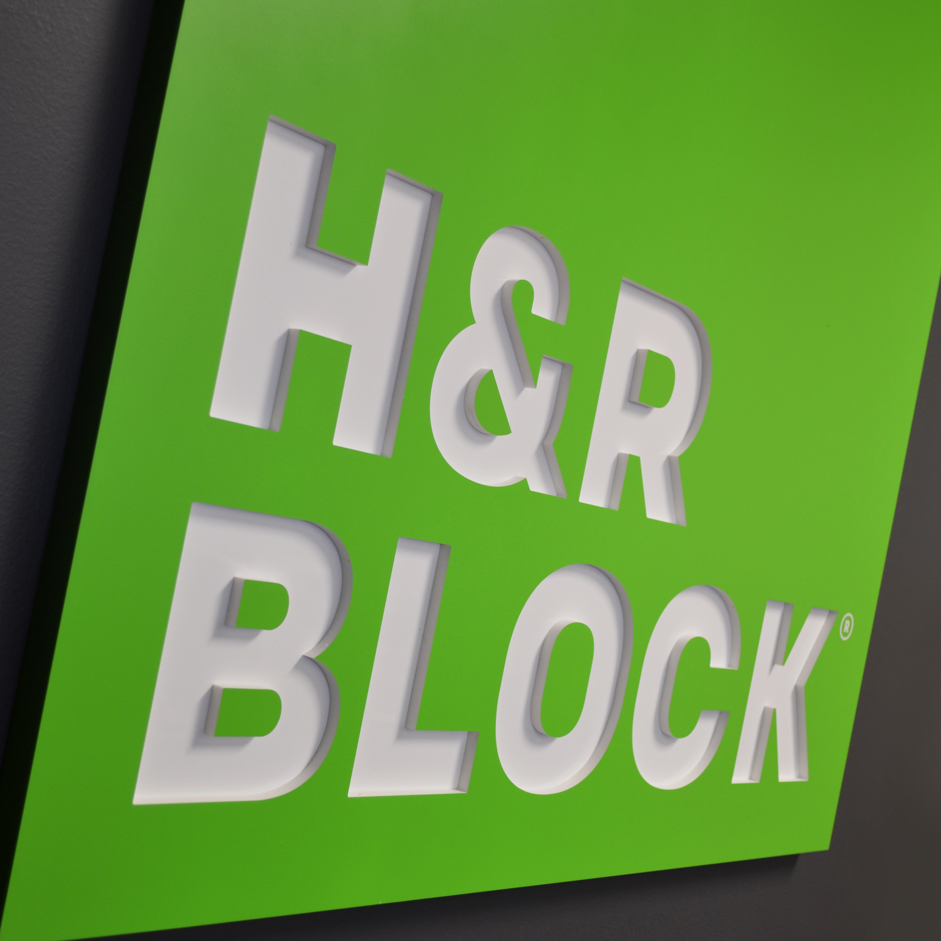 Custom dimensional sign for H&R Block that anchors the branded space.