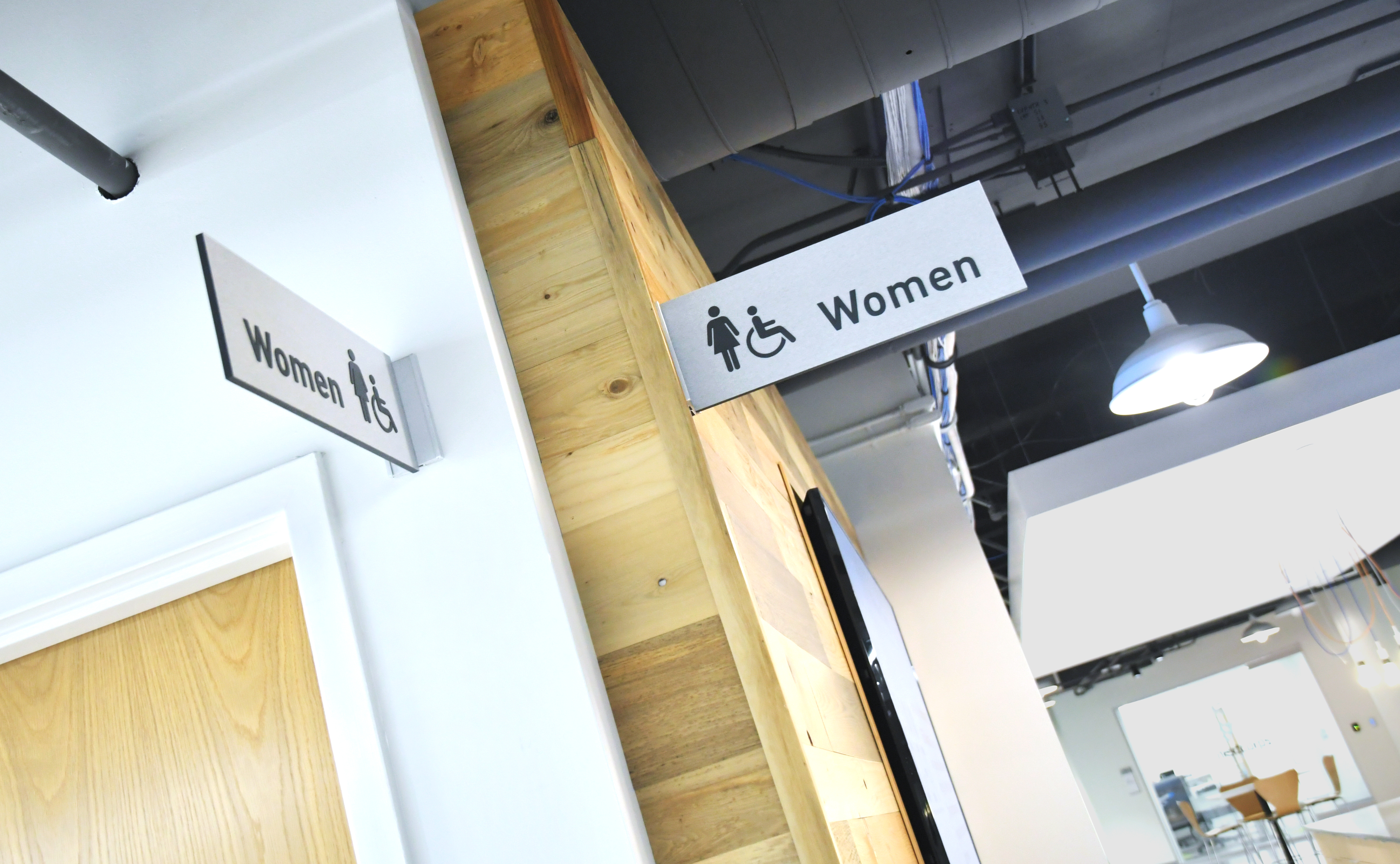 Photo of flag mounted restroom id signs at Nextcorps
