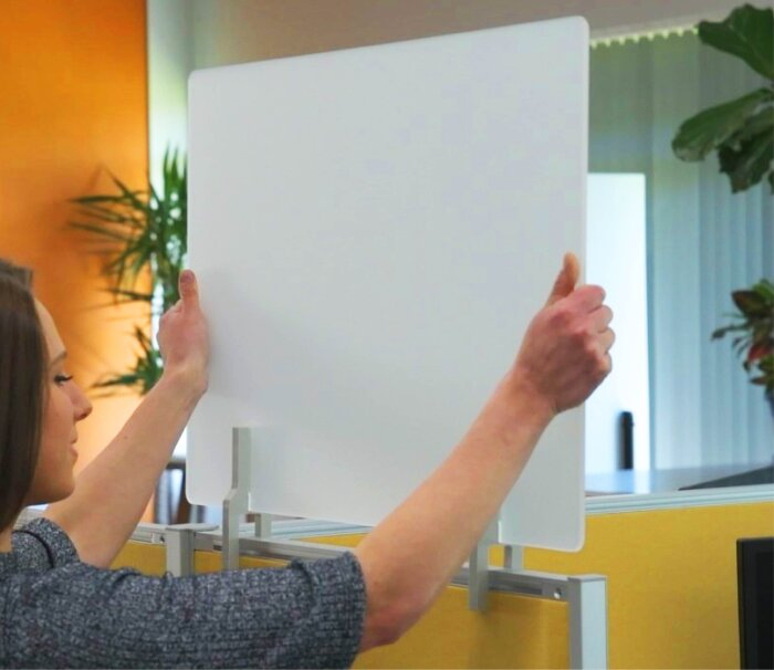 Young woman installs workstation partition with two hands.