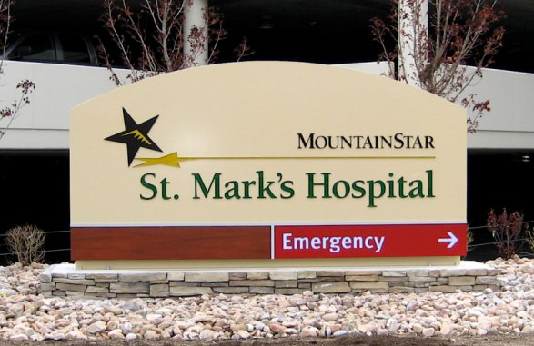 Hospital exterior logo sign with stone facade on footer