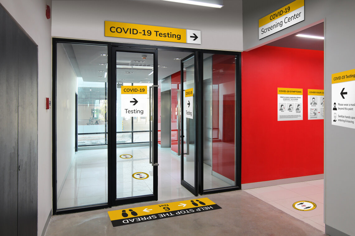 Hospital interior corridor with various COVID-19 messaging displayed by Takeform's Respond Rapid Deployment Sign System