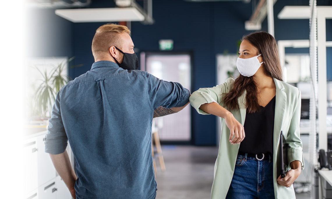 Two coworkers smile under face masks and elbow bump as they walk past eachother