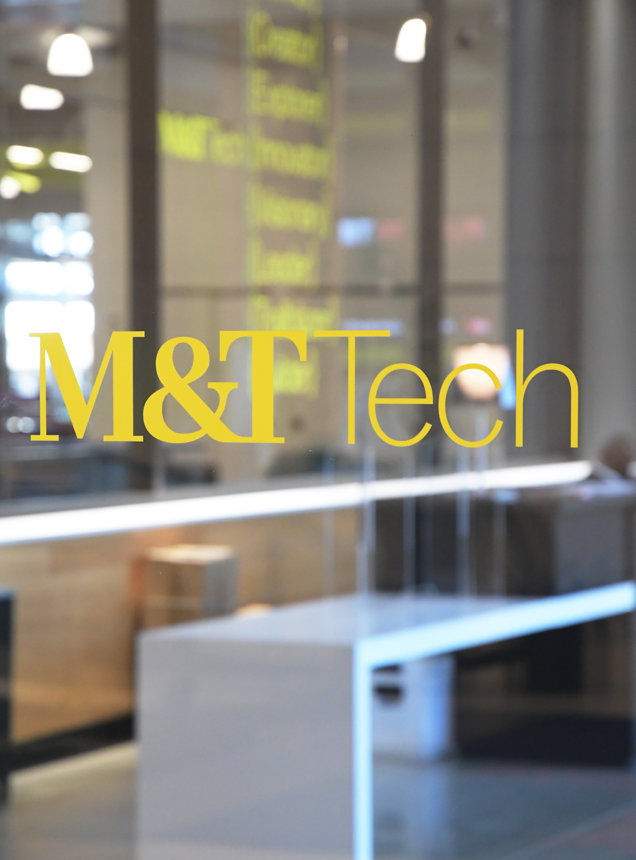 Photo of yellow M and T letters on glass entrance door