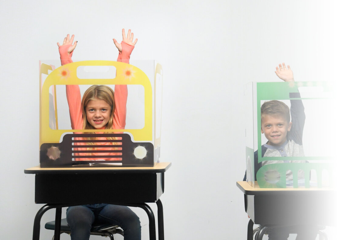 Two young students raise hands behind FunView Desktop Shields