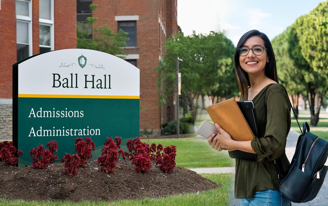 Female student smiles holding books while standing beside exterior signage on campus