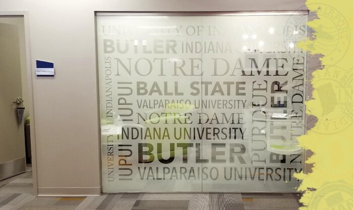 Window film installation featuring names of local universities