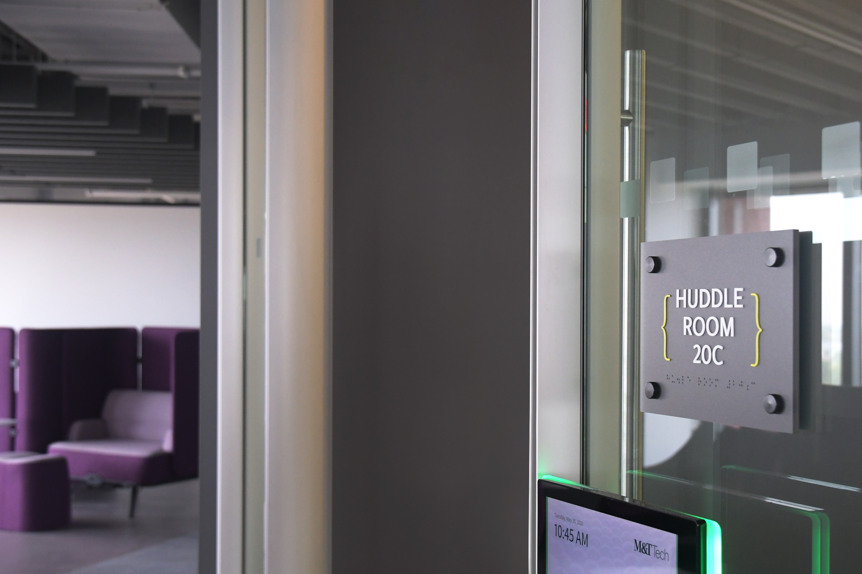 Photo of lounge area and room signage with Ethos lettering