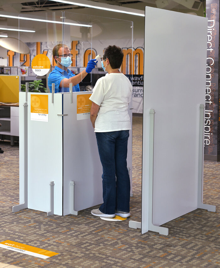 Screener and incoming emplyee in an Adjoin Tempreature Check Station with Screening window, protective partitions, and instructional COVID-related signage