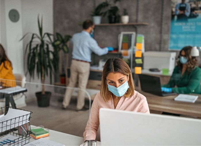 Young professional woman works behind computer in modern office