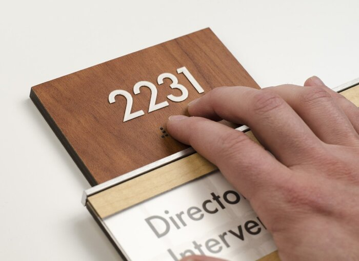 Hand reading braille on an ADA compliant permanent too sign.