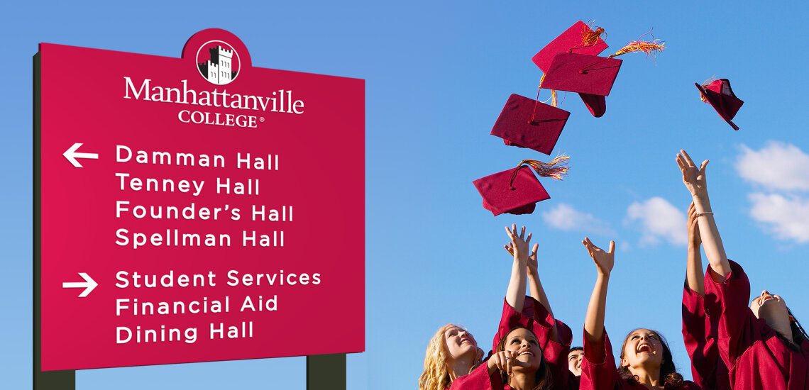 Recent graduates throwing maroon hats into the air next to exterior sign