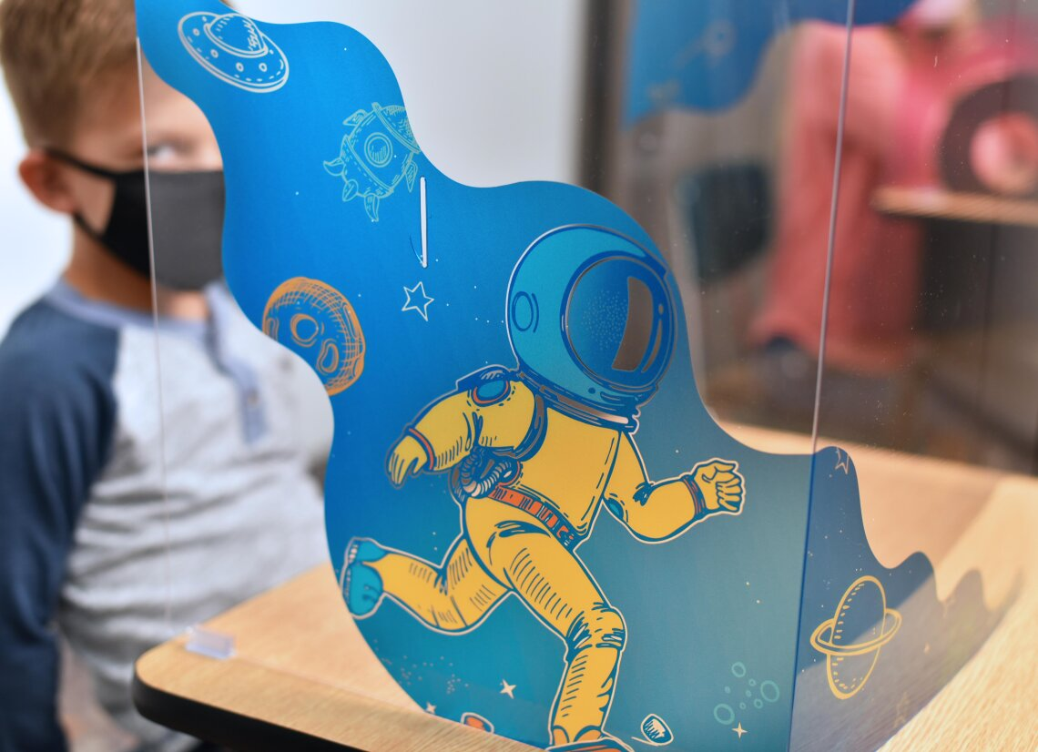 Young boy sits behind FunView Graphic Shield with cartoon of man walking on the moon printed on the face
