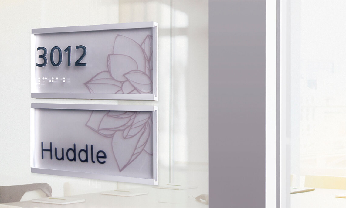 Lucid Room Identification signage accommodates on-glass installation. Shown here is a stacked, two-piece configuration with tactile room numbers, clear Braille, and room name with floral graphic printed on the replacable insert.