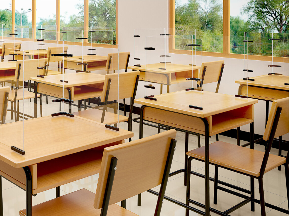 Wooden desks and chairs in modern classroom with 3-sided screens