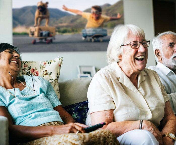 Three friends in a retired living community laugh together on couch