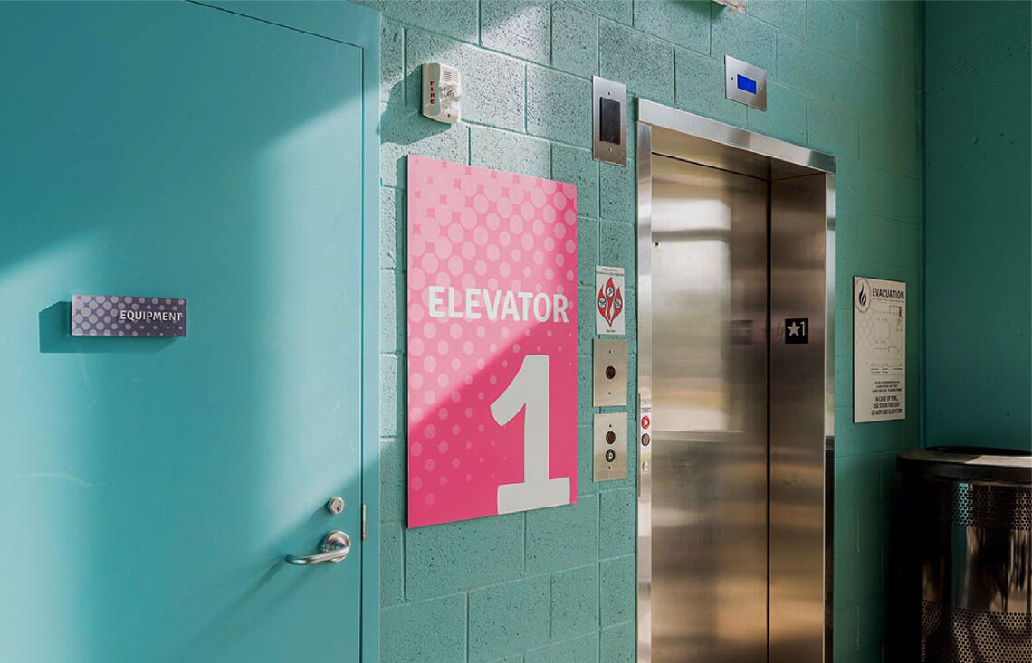 "Pink sign beside elevator in blue parking garage that reads ""1"""