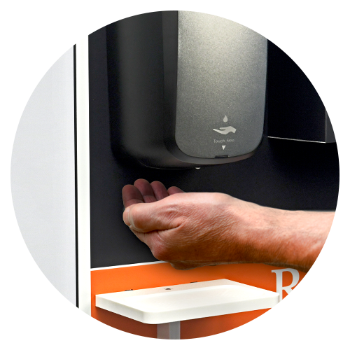 Man's hand waits underneath touch-free sanitizer dispenser